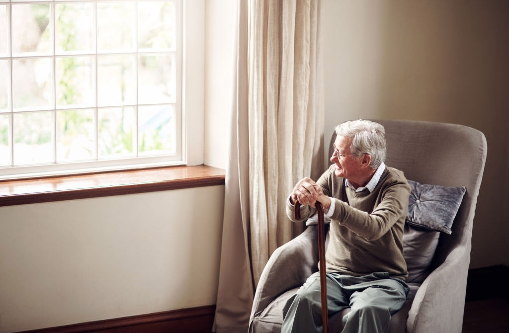 elderly man looking our of the window in a patient care home