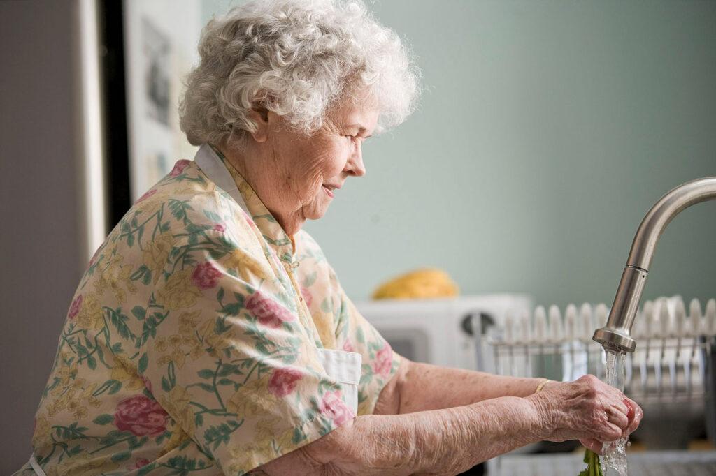 elderly woman washing her hands