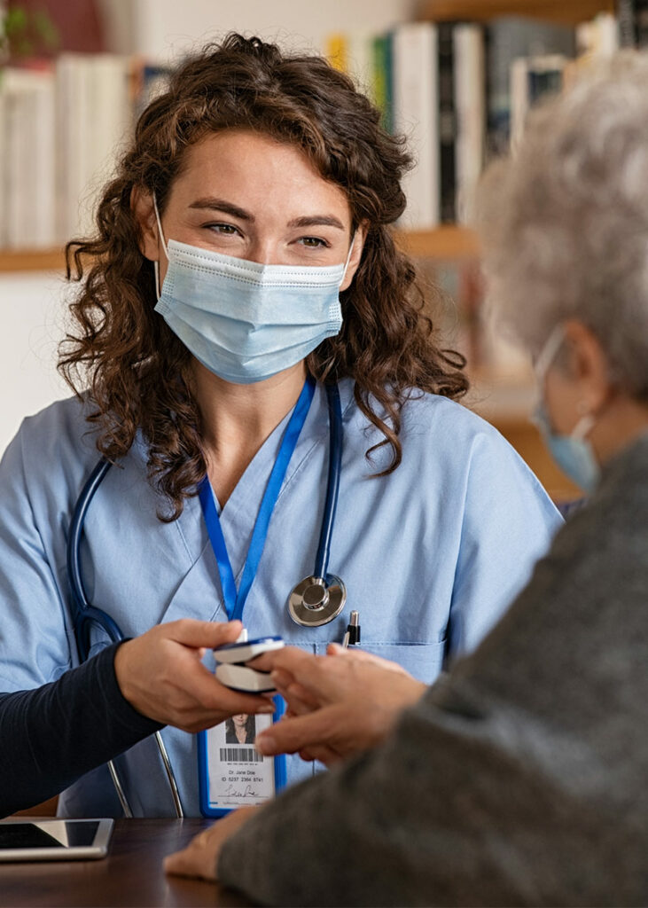 nurse with a mask on talking to an elderly patient