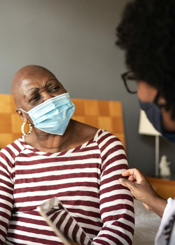 elderly woman with a mask on talking to a nurse in patient care